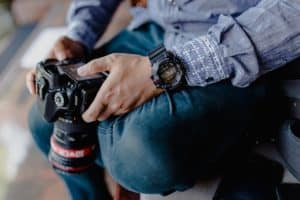 צלם יושב עם המצלמה ביד